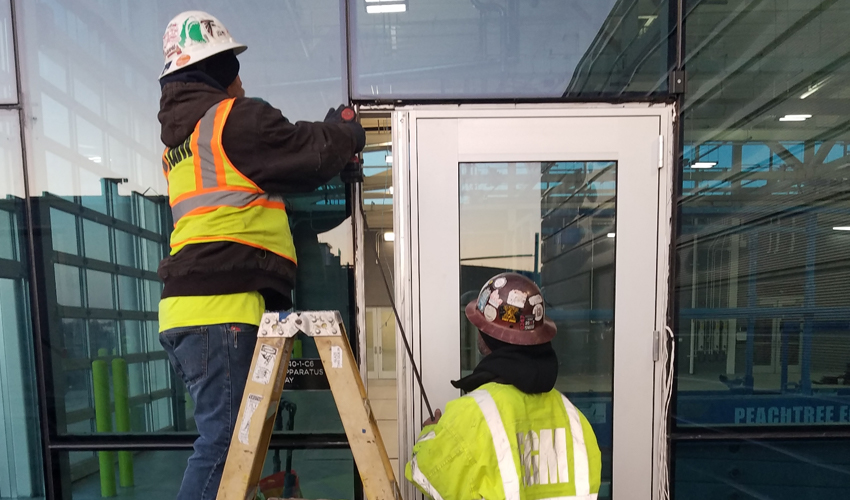 egm workers drilling window pane